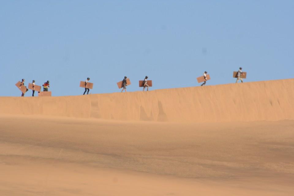 Sandboarders climbing the dunes